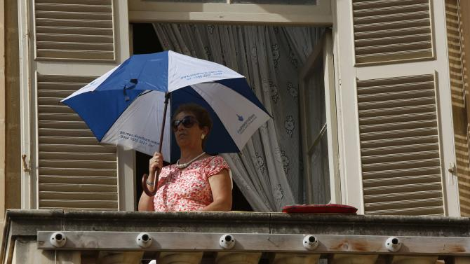 A woman watches from a balcony as Britain's Prince William arrives for High Mass at St John's Co-Cathedral in Valletta