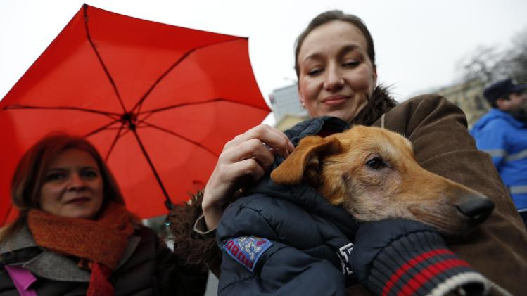 A woman holds her dog during a protest against the culling of stray dogs in Bucharest