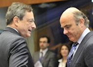 European Central Bank president Mario Draghi (L) speaks with Spanish Finance Minister Luis De Guindos before an Eurozone Coucil at the Kirchberg conference centre in Luxembourg. The eurozone started tackling conditions on Thursday for financial aid to Spain&#39;s banks, while arguing over a revision sought by Greece&#39;s new government of its bailout