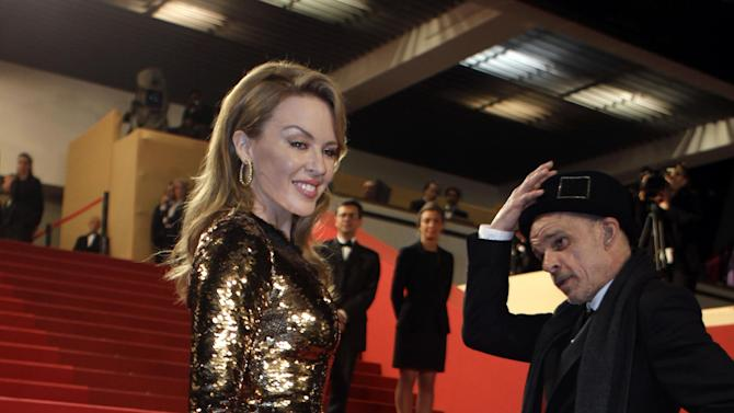 Actor Denis Lavant, right, and Kylie Minogue pose as they arrive for the screening of Holy Motors at the 65th international film festival, in Cannes, southern France, Wednesday, May 23, 2012. (AP Photo/Lionel Cironneau)