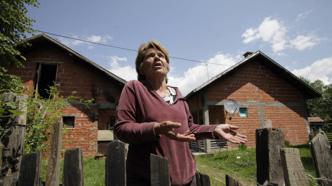 German woman Kristina Siegner stands in front of the house where she has been living with a Bosnian couple who allegedly enslaved and abused her daughter for a number of years, in the village of Karavlasi, 140 kms north of Sarajevo, on Monday, May 28, 2012.  A couple who allegedly beat a young woman while keeping her locked up for years have been arrested in Bosnia, an official said Sunday.  The 19-year-old girl was rescued after villagers tipped off authorities that she was being abused, the spokesman for the prosecutor's office in Tuzla, Admir Arnautovic, told The Associated Press. He said Milenko Marinkovic, 52, and his wife Slavojka, 45, were detained on suspicion of illegal imprisonment in a particularly cruel way. (AP Photo/Amel Emric)