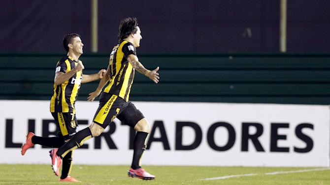 Federico Santander of Paraguay's Guarani celebrates with his teammates Julian Benitez after the former scores against Brazil's Corinthians during their Copa Libertadores soccer match at the Defensores del Chaco stadium in Asuncion