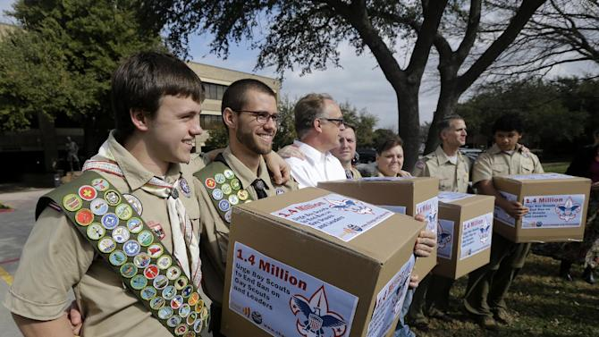 FILE - In this Feb. 4, 2013 file photo, James Oliver, left, hugs his brother and fellow Eagle Scout, Will Oliver, who is gay, as Will and other supporters carry four boxes filled with petitions to end the ban on gay scouts and leaders in front of the Boy Scouts of America headquarters in Dallas, Texas. With its ranks deeply divided, the Boy Scouts of America is asking its local leaders from across the country to decide whether its contentious membership policy should be overhauled so that openly gay boys can participate in Scout units. The proposal to be put before the roughly 1,400 voting members of the BSA's National Council on Thursday, May 23, 2013 at a meeting in Grapevine, Texas, would retain the Scouts' long-standing ban on gays serving in adult leadership positions. (AP Photo/Tony Gutierrez, File)