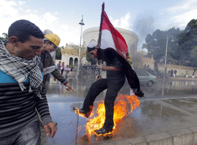 An Egyptian protester tries to escape from fire after he burned an anti-Mohammed Morsi banner in front of the presidential palace in Cairo, Egypt, Friday, Feb. 1, 2013. Thousands of Egyptians marched 
