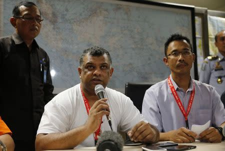 Air Asia CEO Fernandes sits beside Indonesia Air Asia CEO Widyatmoko as they hold a news conference at Surabaya's Juanda International Airport
