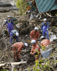 Firefighters search for missing people among collapsed houses following a landslide caused by Typhoon Wipha on Izu Oshima island, south of Tokyo, in this photo taken by Kyodo October 16, 2013. A typhoon killed 17 people in Japan on Wednesday, most on an offshore island, but largely spared the capital and caused no new disaster as it brushed by the wrecked Fukushima nuclear power station, the plant's operator said. Mandatory Credit. REUTERS/Kyodo (JAPAN - Tags: DISASTER ENVIRONMENT) ATTENTION EDITORS - THIS IMAGE WAS PROVIDED BY A THIRD PARTY. THIS PICTURE IS DISTRIBUTED EXACTLY AS RECEIVED BY REUTERS, AS A SERVICE TO CLIENTS. FOR EDITORIAL USE ONLY. NOT FOR SALE FOR MARKETING OR ADVERTISING CAMPAIGNS. MANDATORY CREDIT. JAPAN OUT. NO COMMERCIAL OR EDITORIAL SALES IN JAPAN. YES
