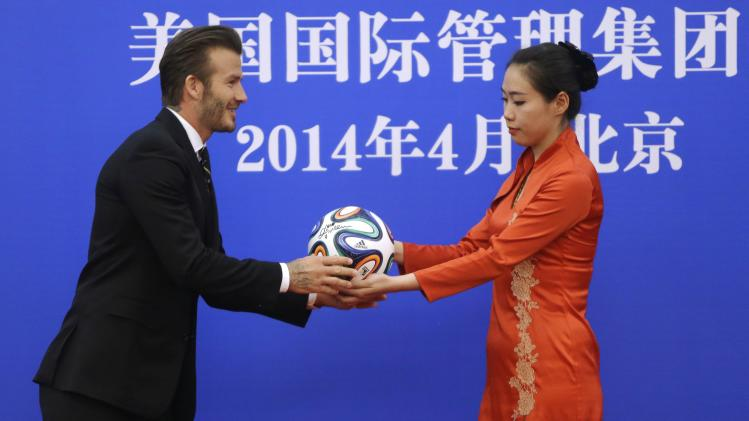 An attendant passes a soccer ball to former captain of England soccer team David Beckham during a ceremony at the Great Hall of the People in Beijing