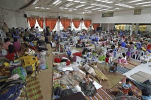 People take shelter inside a evacuation center after evacuating their homes due to super-typhoon Hagupit in Surigao city, southern Philippines