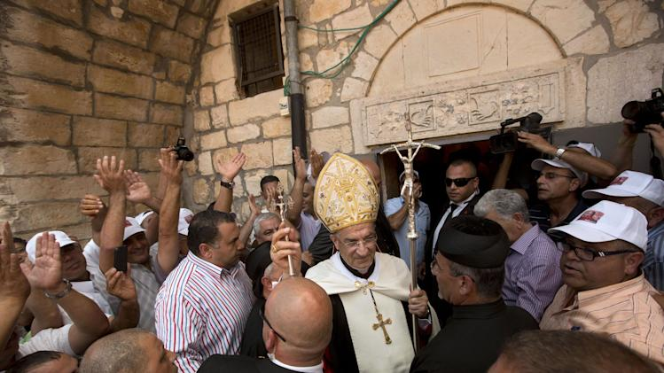 Cardinal Bechara Rai, the head of Lebanon's Maronite Catholics, marches with supporters to a church in the ruins of the village of Kufr Birim, northern Israel, Wednesday, May 28, 2014. It was one of two politically charged visits to disparate Maronite flocks in Israel Wednesday in a precedent-setting Holy Land pilgrimage overshadowed by criticism back home. Israeli forces demolished Kufr Birim in 1953, five years after persuading hundreds of residents to leave with the promise of a speedy return that never materialized. (AP Photo/Sebastian Scheiner)