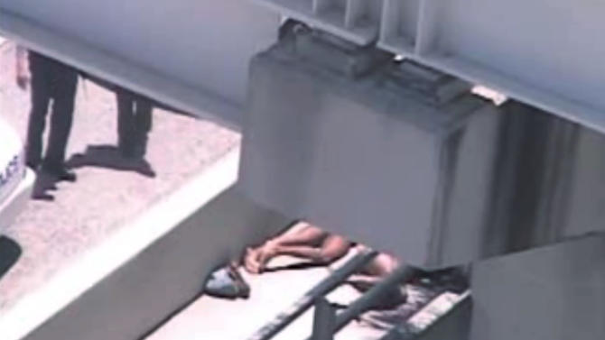 FILE - In this Saturday, May 26, 2012 file image taken from video, Miami police officers stand watch near a naked man, second from right, who was shot dead by a police officer when he refused to stop chewing on the face of the naked man next to him, partially obscured by a railing, on the MacArthur Causeway ramp onto Northeast 13th Street in Miami. Several people called 911 after seeing events related to the vicious attack, according to recordings released by authorities Friday, June 1, 2012. (AP Photo/The Miami Herald, File)  MAGS OUT
