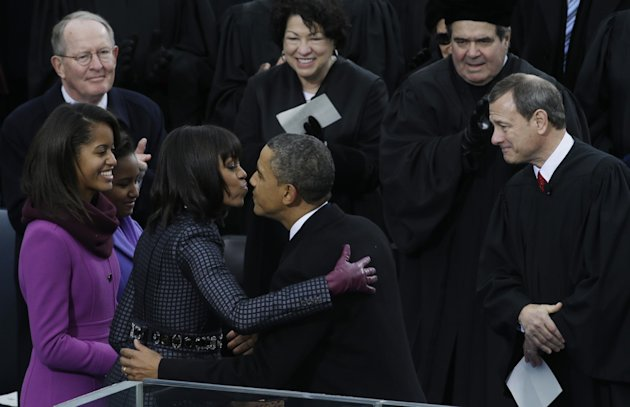 President Barack Obama kisses his wife Michelle after the ceremonial swearing-in at the U.S. Capitol during the 57th Presidential Inauguration in Washington, Monday, Jan. 21, 2013. Right is Chief Justice John Roberts. (AP Photo/Paul Sancya)