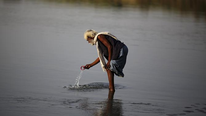 A man searches for valuables in the water of river Yamuna in New Delhi