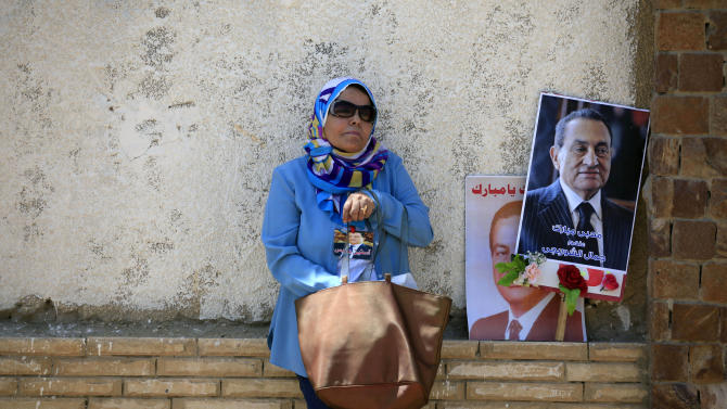 """A supporter of Egypt's ousted President Hosni Mubarak, pictured, attends a rally outside a courtroom in Cairo, Egypt, Saturday, May 11, 2013. Egyptian prosecutors say they are presenting new evidence in the retrial of Mubarak. The former president, all in white and wearing sunglasses, attended the hearing in the courtroom defendants' cage alongside his two sons and former interior minister, who was in charge of police at the time. Arabic writing on the poster at right reads, """"Jamal al-Shorbaji on behalf of Mubarak lovers."""" (AP Photo/Khalil Hamra)"""