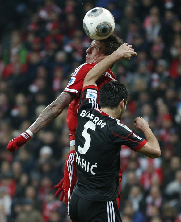 Bayern's Mario Mandzukic of Croatia, rear, and Leverkusen's Emir Spahic of Bosnia challenge for the ball during the German first division Bundesliga soccer match between FC Bayern Munich and B