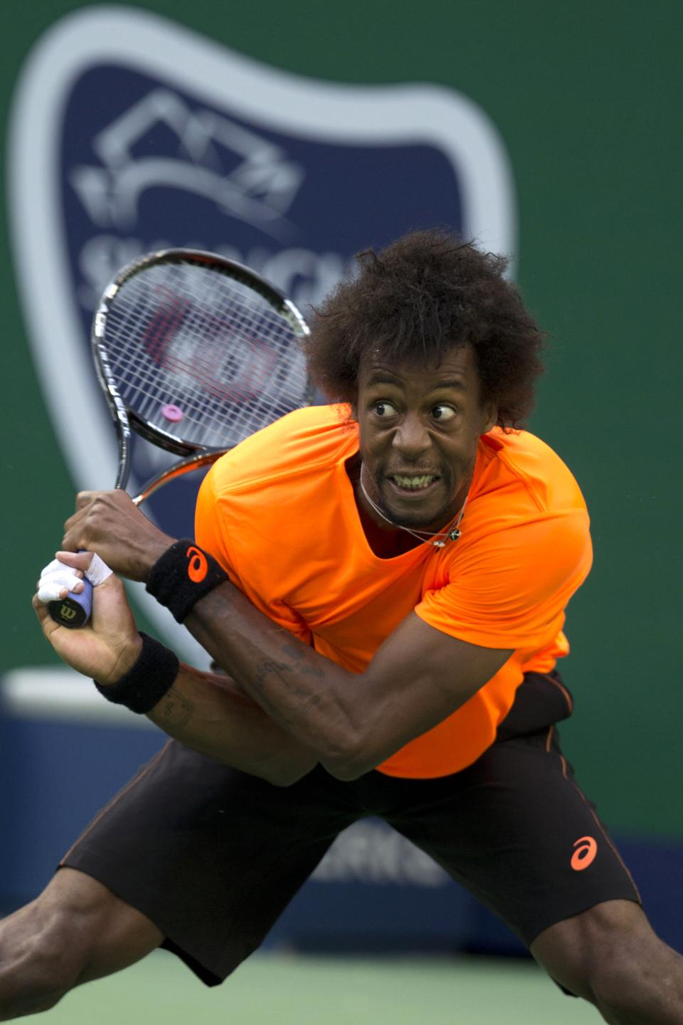 France's Gael Monfils returns a shot during a match against Switzerland's Roger Federer at the Shanghai Masters tennis tournament at the Qizhong Forest Sports City Tennis Center in Shanghai, China, Thursday, Oct. 10, 2013. Monfils won 6-4, 6-7, 6-3. (AP Photo/Ng Han Guan)