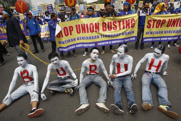 "Indonesian workers with their faces and bodies painted in white and an Indonesian word ""Buruh"" that means ""Workers"" in red take part in a rally commemorating May Day in Jakarta, Indonesia, Wednesday,"