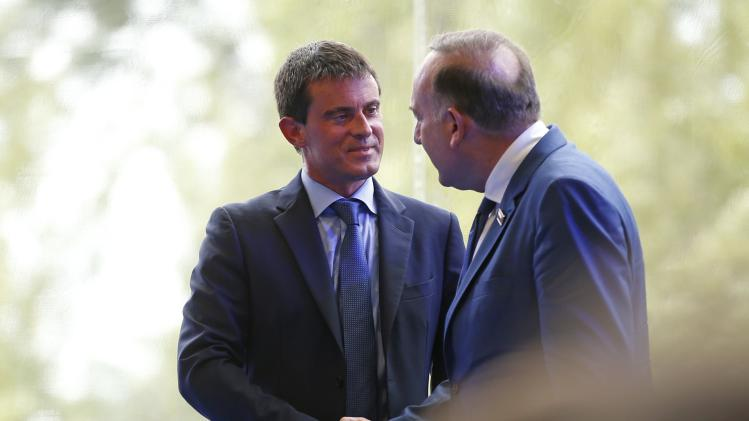 French employer's body MEDEF union leader Pierre Gattaz shakes hands with French Prime Minister Manuel Valls after his opening speech during the MEDEF summer forum on the campus of the HEC School of Management in Jouy-en-Josas