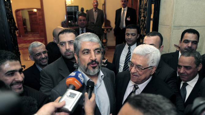In this Feb. 22, 2012 file photo, Palestinian President Mahmoud Abbas, center right, and Hamas leader Khaled Mashal talk to reporters following their meeting in Cairo, Egypt. An unprecedented gathering of top Palestinian politicians and academics this week suggests the split between Islamists and secular nationalists has hardened into permanence. Despite ongoing negotiations with Israel by President Mahmoud Abbas there is a clear sense, in both his Fatah and its Islamist rival Hamas, of a national movement that is fragmented and in crisis. (AP Photo/Amr Nabil, File)