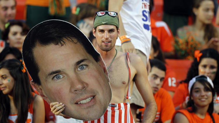 A Miami fan holds a photo of Miami head coach Al Golden before an NCAA college football game against Florida State in Miami, Saturday, Oct. 20, 2012. (AP Photo/Alan Diaz)