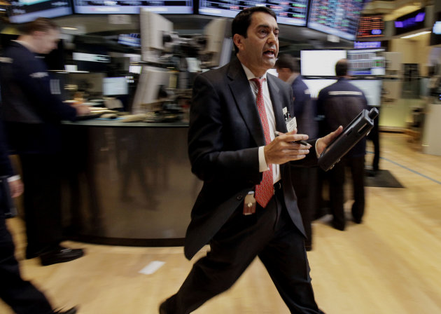 FILE - In this June 1, 2012, file photo, Trader Mark Muller scurries across the floor of the New York Stock Exchange. The global economy's foundations are weakening, one by one. Already hobbled by Europe's debt crisis, the world now risks being hurt by slowdowns in its economic powerhouses. With fears of another global economic downturn, investors are sending their money to higher ground _ government bonds in the U.S. and Germany. (AP Photo/Richard Drew, File)