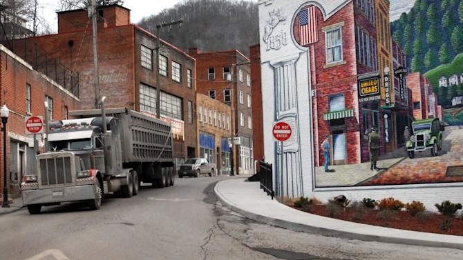 FILE - In this Feb. 9, 2011, file photo, a coal truck drives out of downtown Welch, W.Va. A record number of U.S. counties _ more than 1 in 3 _ are now dying off, hit by an aging population and weakened local economies that are spurring young adults to seek jobs elsewhere. New 2012 census estimates highlight the population shifts as the U.S. encounters its most sluggish growth levels since the Great Depression. In the last year, Maine joined West Virginia as the only two entire states where deaths exceed births, which have dropped precipitously after the recent recession.  (AP Photo/Jon C. Hancock, File)
