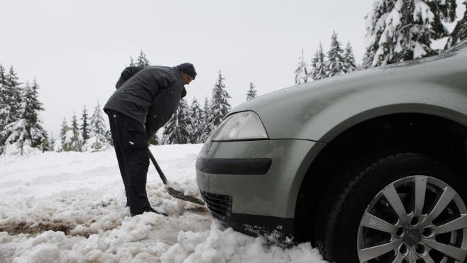 A Bosnian man shovels snow in front of a car stuck in snow near Sarajevo, Bosnia, on Monday, May 14, 2012. Heavy snow covered central parts of Bosnia early Monday. After the weekend with record high temperatures, reaching mid 30's Celsius, citizens of Sarajevo woke up Monday with 10 centimeters of snow covering the city streets. (AP Photo/Amel Emric)