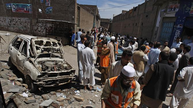 People gather at the site of an explosion outside an election office of a candidate in Peshawar, Pakistan, Sunday, April 28, 2013. Pakistani Taliban detonated bombs at the campaign offices of two politicians in the country's northwest on Sunday, police said, killing many people in an escalation of attacks on secular, left-leaning political parties. (AP Photo/Mohammad Sajjad)