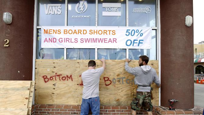 Store manager L.P. Cyburt, right, gets help boarding up the windows of the business as Hurricane Sandy approaches the Atlantic Coast, in Ocean City, Md., on Saturday, Oct. 27, 2012. (AP Photo/Jose Luis Magana)