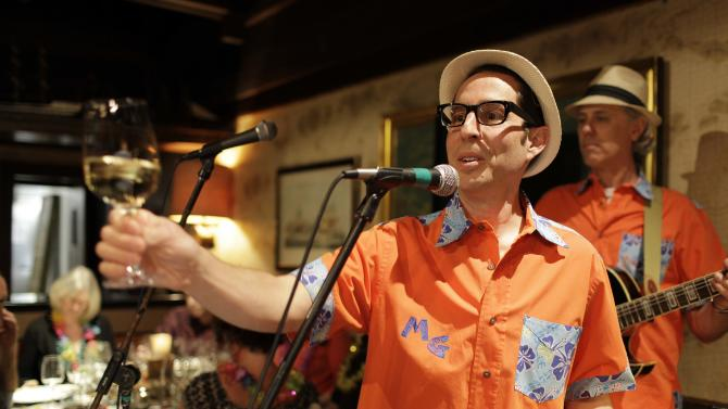 In this photo taken Friday, March 23, 2012, winemaker Judd Finkelstein of Judd's Hill winery, makes a toast before playing his ukulele with his band during a winery luau at Trader Vic's restaurant in Emeryville, Calif. Don't be surprised if Finkelstein serenades you with a ukulele. Playing the uke is one of his passions, he performs with his group Maikai Gents featuring The Mysterious Miss Mauna Loa. (AP Photo/Eric Risberg)