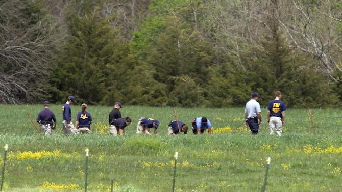 Law enforcement officials scan the fields behind a farm Thursday, May 9, 2013 in search of an18-month-old baby in rural Ottawa, Kan., where three bodies were found on Monday.  Authorities in eastern Kansas said Thursday they have arrested a 27-year-old suspect in the deaths of three people whose bodies were found at a farm, and that a fourth victim — an 18-month-old girl — is presumed dead. (AP Photo/The Topeka Capital Journal, Chris Neal)