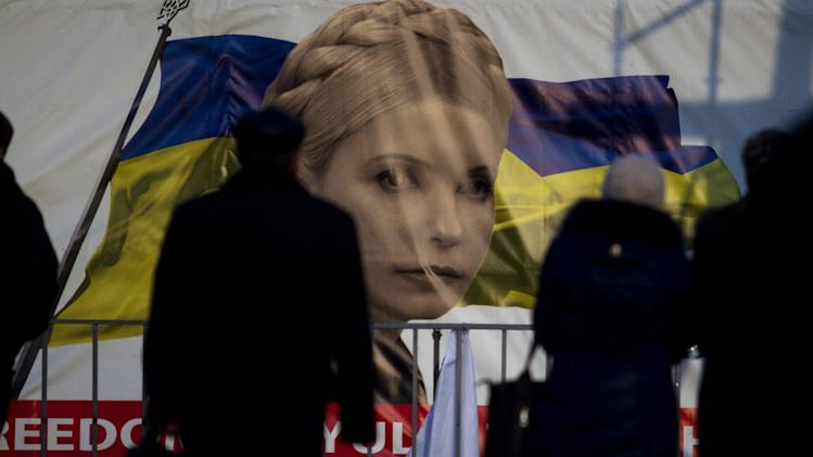 People pass by a portrait of Yulia Tymoshenko, a prominent opposition leader at Independence Square in Kiev, Ukraine, Monday, Feb. 24, 2014. Ukraine's acting government issued a warrant Monday for the arrest of President Viktor Yanukovych, last reportedly seen in the pro-Russian Black Sea peninsula of Crimea, accusing him of mass crimes against protesters who stood up for months against his rule. (AP Photo/Marko Drobnjakovic)