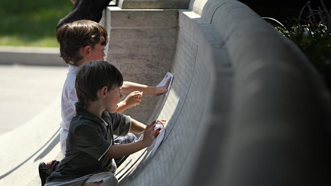FILE- In an Aug. 18, 2009 file photo, Isaiah Sabounjian, 5, left, and his brother Tyler Sabounjian, 5, of Silver Spring, Md., make rubbings of their grandfather's name, Capitol Police Sgt. Christopher Eney, who was accidentally killed during a SWAT training exercise in Washington in 1984, after a ceremony honoring Eney on the 25th anniversary of his death at the National Law Enforcement Officers Memorial in Washington. Tough calls don't often confront the people responsible for deciding who belongs on a national memorial for officers killed in the line of duty. But recognizing fallen men and women in blue isn't always a black-and-white decision. The cases of two inductees this year highlight challenges for the National Law Enforcement Officers Memorial Fund. It holds a vigil Monday, May 13, 2013, for 321 officers added to the wall. (AP Photo/Jacquelyn Martin, File)