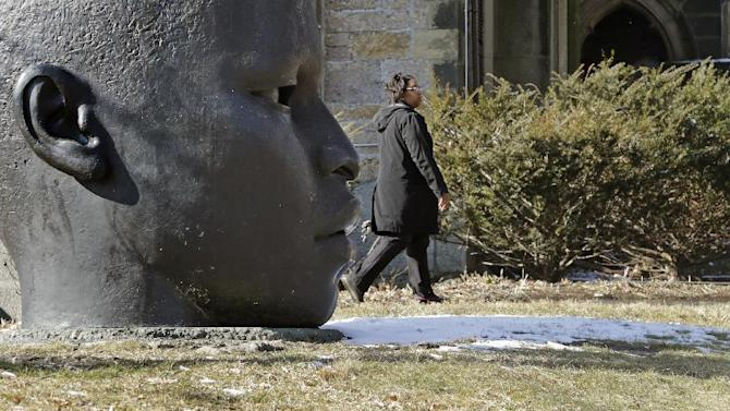 "A woman walks on the partially snow-covered grass outside the National Center of Afro-American Artists in the Roxbury neighborhood of Boston, Wednesday, Feb. 6, 2013.  A midwinter storm headed to the Northeast on Friday could drop more than a foot of snow.  The sculpture at left is ""Eternal Presence"", by John Wilson. (AP Photo/Charles Krupa)"