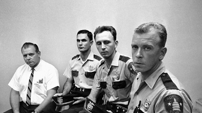 FILE - In this Aug. 2, 1966 file photo, from left, Allen Crum, university co-op employee; Austin policemen Ramiro Martinez, Houston McCoy and Jerry Day, the four men who braved the deadly accurate sniper fire by Charles Joseph Whitman from the University of Texas tower, meet with newsmen in Austin, Texas.  McCoy, the Austin police officer who fired two blasts from his shotgun to bring down Whitman, has died. (AP Photo/Ted Powers, File)