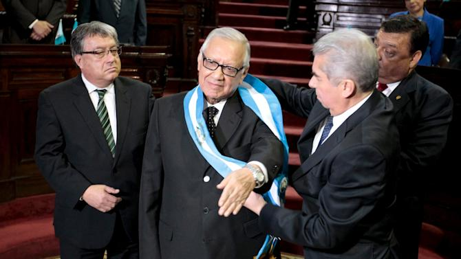 Alejandro Maldonado, the new Guatemalan President, receives the presidential sash from Rabbe, as lawmakers Fajardo and Herrera, look on during a sworn in ceremony at the Congress in Guatemala City