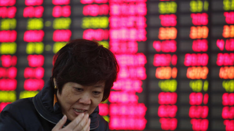 An investor speaks in front of the stock price monitor at a private securities company Wednesday Nov. 27, 2013 in Shanghai, China. Asian stocks were muted Wednesday as funds switched to better performing markets and trading thinned out ahead of the Thanksgiving holiday in the U.S. (AP Photo)