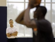 Charlotte Bobcats new head coach Mike Dunlap, left, watches Bismack Biyombo, right, during an NBA basketball practice in Charlotte, N.C., Thursday, June 21, 2012. (AP Photo/Chuck Burton)