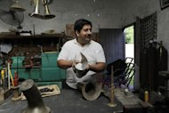 "In this Dec. 8, 2012 photo, Tito Romero demonstrates how he makes a trumpet with recycled metal in his workshop at his home in Capiata, Paraguay. Romero was repairing damaged trumpets in a shop outside Asuncion until Favio Chavez, the creator of ""The Orchestra of Instruments Recycled From Cateura,"" asked him to turn galvanized pipe and other pieces of metal into flutes, clarinets and saxophones for his students. (AP Photo/Jorge Saenz)"