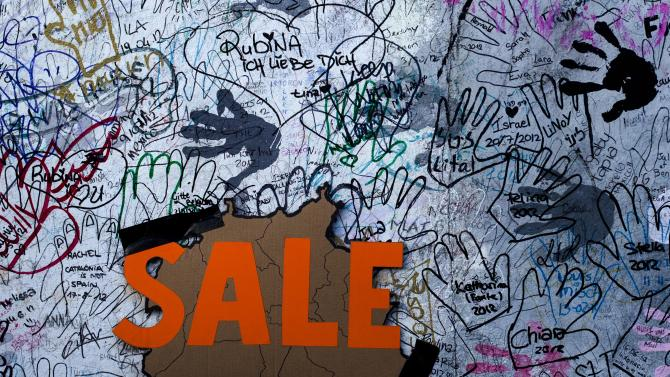 A 'Sale' sign with the form of Germany's capital Berlin is fixed  amid graffiti on the East Side Gallery section of the former Berlin Wall in Berlin, Monday, March 4, 2013. After massive protest an investor suspended the removal of a section of the historic stretch of the Berlin Wall known as the East Side Gallery to provide access to a riverside plot where luxury condominiums are being built. (AP Photo/Markus Schreiber/Pool)