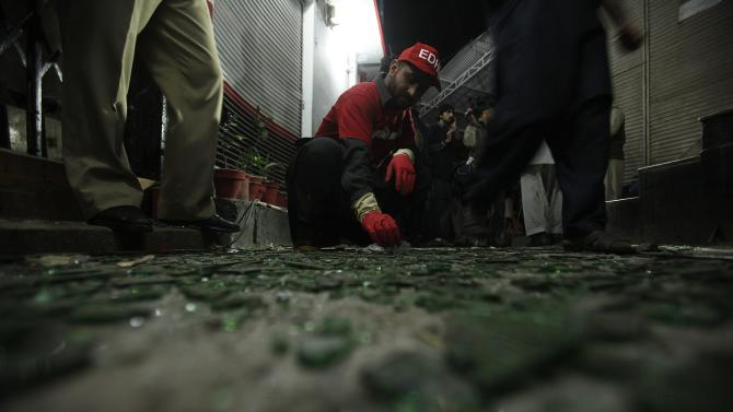 A rescue worker collects evidence at the site of a bomb blast in Peshawar