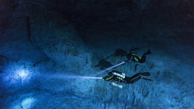 """In this June 2013 photo provided by National Geographic, divers make their way toward Hoyo Negro, an underwater cave in Mexico's Yucatan Peninsula where the remains of """"Naia,"""" a teenage girl who lived 12,000 to 13,000 years earlier, were found. Her skeleton and her DNA are helping scientists study the origins of the first Americans. An analysis of her remains was released Thursday, May 15, 2014 by the journal Science. Her DNA links her to an ancient land bridge connecting Asia and North America, and suggests she shares ancestors with the modern native peoples of the Americas.(AP Photo/National Geographic, Paul Nicklen)"""