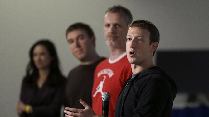 "Facebook CEO Mark Zuckerberg, right, speaks with Director of Product Management Tom Stocky, second from left, and Director of Engineering Lars Rasmussen at Facebook headquarters  in Menlo Park, Calif., Tuesday, Jan. 15, 2013. Zuckerberg introduced ""graph search"" Tuesday, a new service that lets users search their social connections for information about their friends' interests, and for photos and places.  (AP Photo/Jeff Chiu)"