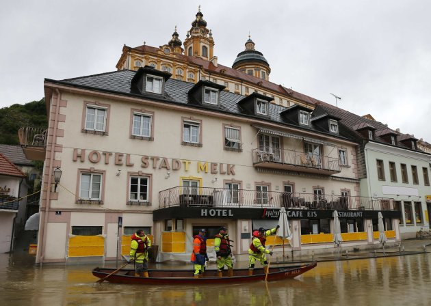 Members of the emergency services travel by boat along a flooded street in the Austrian town of Melk