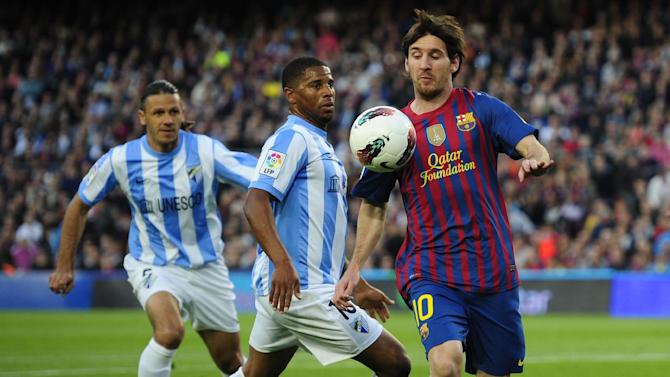 FILE - In this May 2, 2012, file photo, FC Barcelona's Lionel Messi, from Argentina, right, duels for the ball against Malaga's Eliseu Pereira, center, during a Spanish La Liga soccer match at Camp Nou stadium in Barcelona, Spain. United States soccer fans will start noticing less matches available on their television sets in August as television rights to Spain's La Liga switch from GolTV to the new beIN Sport USA network, launched by the Al-Jazeera Sport Media Network and available only in about 8 million homes to viewers of DirecTV and DISH Network. (AP Photo/Manu Fernandez, File)
