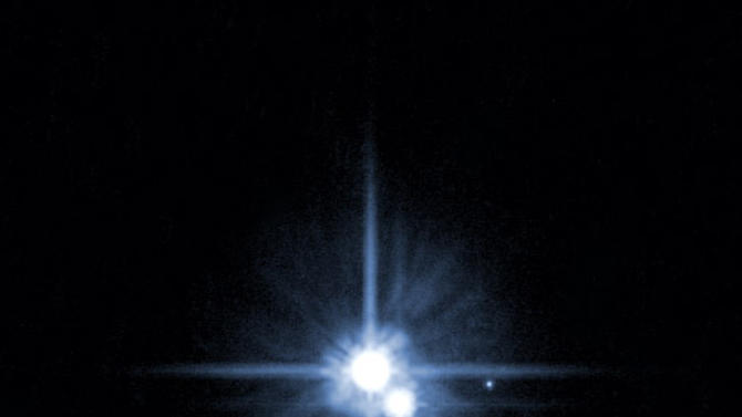 "FILE - This file image provided by NASA on Feb. 22, 2006 from it's Hubble Space Telescope shows Pluto and three of it's five moons.  An online vote to name Pluto's two newest, itty-bitty moon concluded Monday, Feb. 25, 2013, and the winner is Vulcan, a name suggested by actor William Shatner, who played Capt. Kirk in the original ""Star Trek"" TV series.  (AP Photo/NASA, File)"