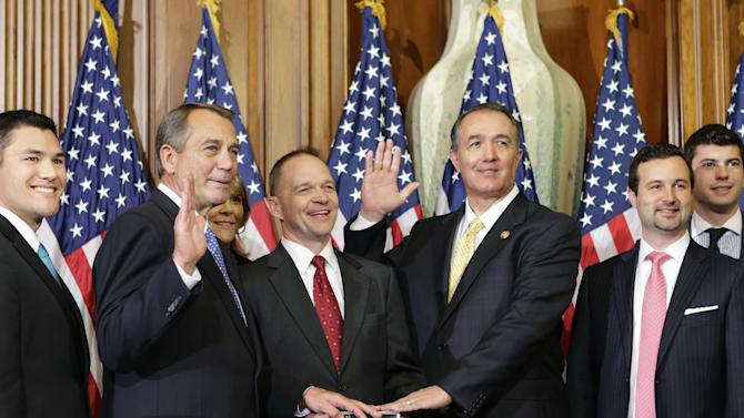 """FILE - In this Jan. 3, 2013, file photo, Rep. Trent Franks, R-Ariz., center right, stands with his family for a ceremonial photo with Speaker of the House John Boehner, R-Ohio, center left, in the Rayburn Room of the Capitol after the new 113th Congress convened in Washington. The nation's sharp disagreements over taxes and spending are on a re-routed collision course, as Senate Democrats launch a plan that includes new taxes, and House Republicans vow to speed up their plan to balance the federal budget with spending cuts alone. """"The American people will have a chance to compare the two approaches,"""" said Franks, who wants deep spending cuts and no new taxes. The only way to shrink the government, he said, """"is to choke the monster.""""  (AP Photo/J. Scott Applewhite, File)"""