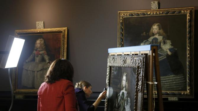 """Employees of Vienna's Art History Museum check the painting """"Infanta Margarita in a green silver dress"""" by Juan Bautista Martinez del Mazo in Vienna"""