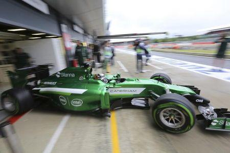 Caterham Formula One driver Kobayashi of Japan drives out from the pits during final practice ahead of the British Grand Prix at the Silverstone Race Circuit