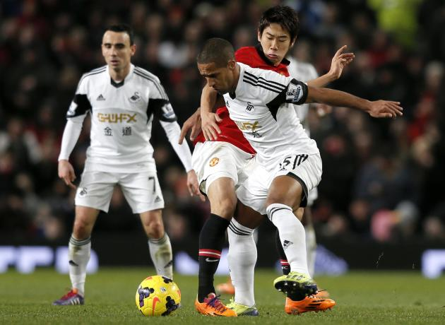 Manchester United's Kagawa challenges Swansea City's Routledge during their English Premier League soccer match at Old Trafford in Manchester