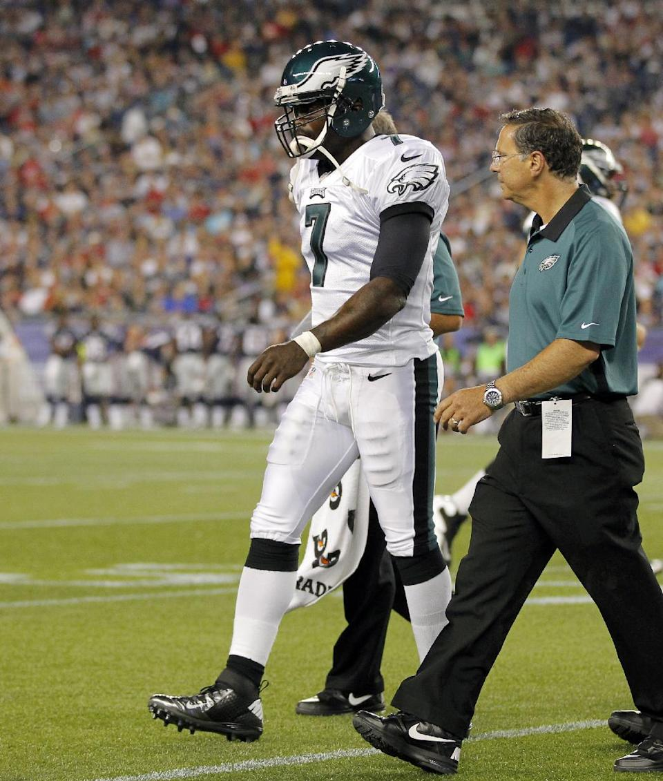 Philadelphia Eagles quarterback Michael Vick (7) is helped off the field after taking a hard hit against the New England Patriots during the first quarter of an NFL preseason football game in Foxborough, Mass., Monday, Aug. 20, 2012.(AP Photo/Steven Senne)